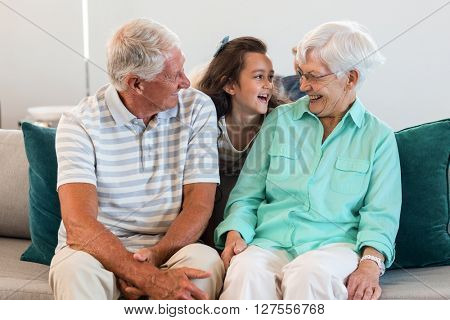 Grandmother and grand father with their granddaughter sitting on sofa in living room