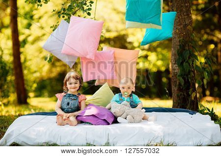 Two children brother and sister having fun in a sunny summer garden with colorful pillows. Little girl and baby boy playing in park tossing pillows.