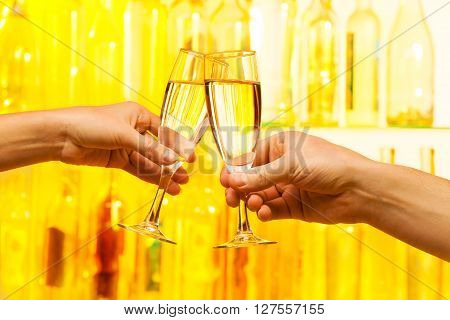 Man and woman hands holding glossy  champagne glasses, romantic scene