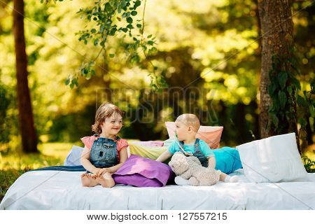 Two children brother and sister having fun in a sunny summer garden with colorful pillows. Little girl and baby boy playing in park.