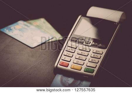 Color image of a POS and credit cards.