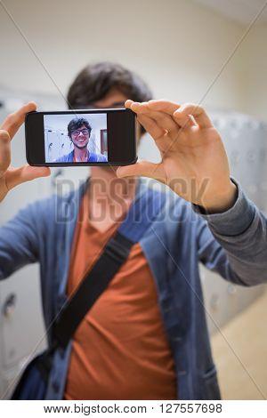 Student taking his selfie on smartphone in locker room