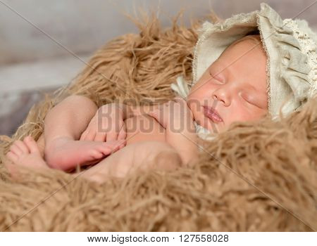 newborn bare baby in hat sleeping on fluffy blanket