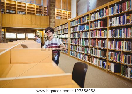 Portrait of happy young student using his laptop in college library