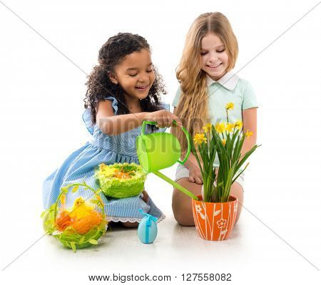two little smiling girls watering flowers and playing on the floor isolated on white background