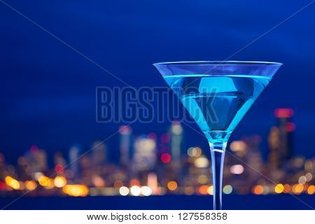 Close-up photo of full cup of martini against the view of city lights at the evening