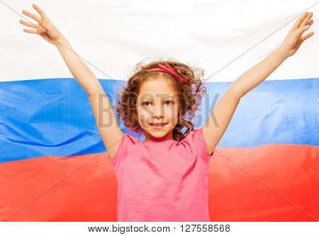 Curly-haired girl raising her hands up, flag of Russian Federation behind