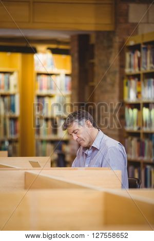 Professor sitting on desk using his laptop in college library