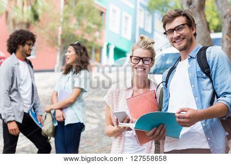 Portrait of students holding book while their friends interacting in the background