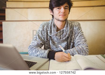 Portrait of young student sitting on desk reading notes in the classroom