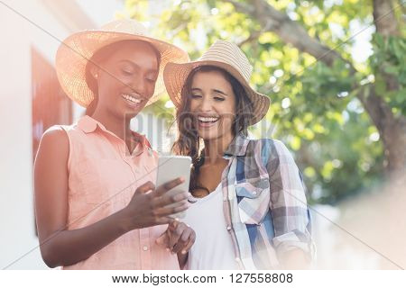 Happy young women using mobile phone