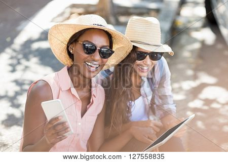 Young women having fun while using digital tablet and mobile phone