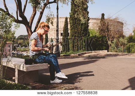 Young woman sitting near Colosseum in Rome, Italy