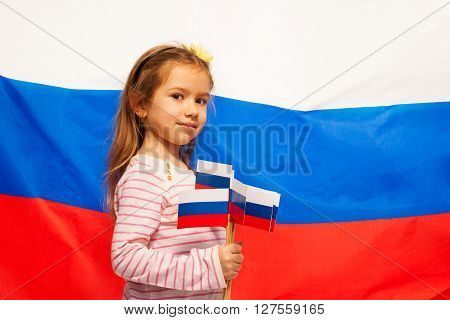 Little girl standing sideways against the flag of Russian Federation holding a lot of flags in her right hand