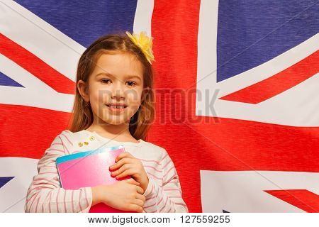 Close-up photo of young girl with textbooks standing against flag of Great Britain
