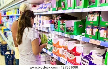 CYPRUS, PROTARAS, SUPERMARKET LIDL - 19.09.2015: Customers choising dairy products in a supermarket