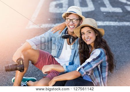 Portrait of happy young couple in hat sitting on road