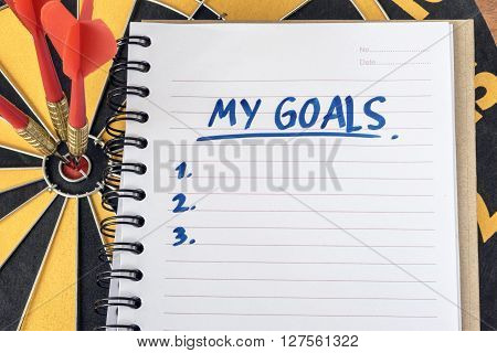 Words my goals on recycle notebook with three dart on bullseye target in dartboard background with copy space business success concept