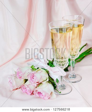 Two glasses of champagne and a bouquet of roses on a background of silk draperies