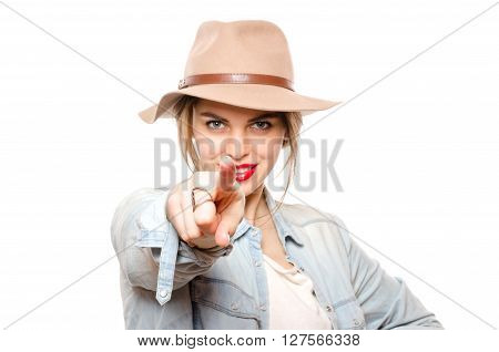 Beautiful young woman in hat pointing at camera standing isolated on white background. Smiling and looking into the camera
