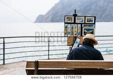 Monterosso Italy - Apr 8 2016: Unidentified street artist selling his landscape painting souvenirs by the ocean at Monterosso Cinque Terre Italy