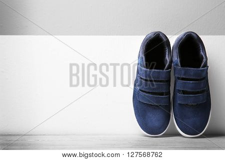 Black sneakers for kid on wall background