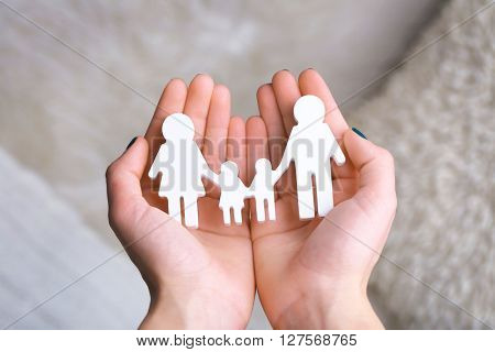 Cutout figurine of a family in female hands closeup