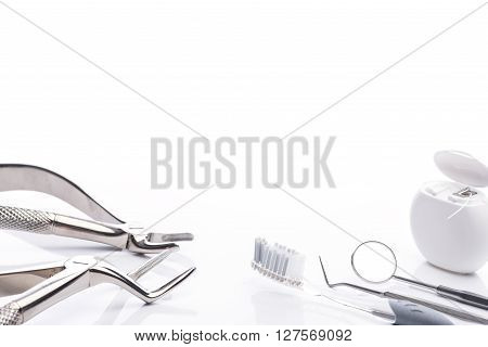 Forceps, Toothbrush, Dental Floss, Mouth Mirror And Dental Probe On White Background
