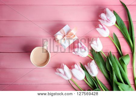 Bouquet of fresh tulips with coffee and present box on pink wooden background