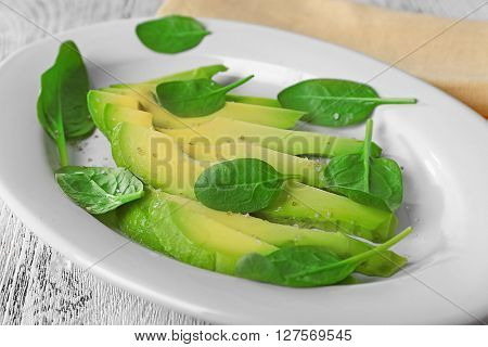 Slices of fresh avocado on plate closeup
