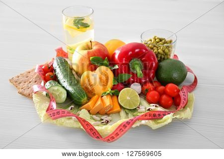 Fresh fruits, vegetables and measuring tape on wooden table closeup