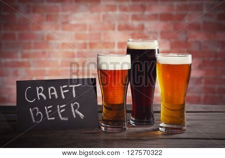 Glasses with different sorts of craft beer on brick wall background. Retro stylization