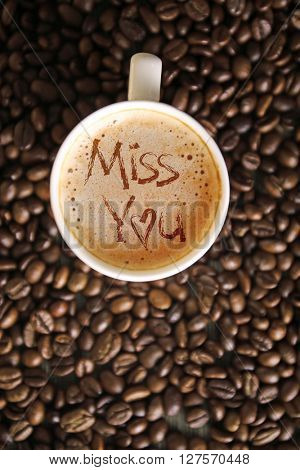 Cup of coffee with words Miss You on foam, top view
