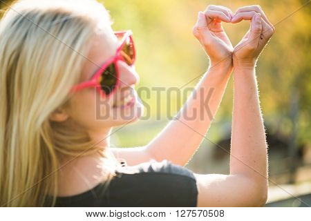 Blonde young girl holding hands in heart shape framing. Blonde woman posing outdoor.