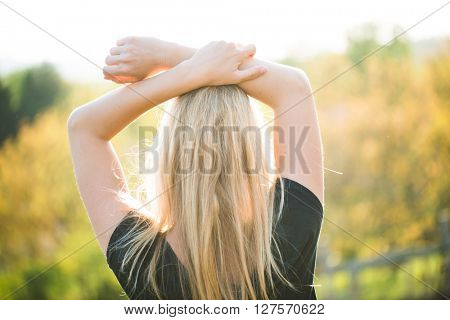 Blonde woman posing outdoor at sunset. Watching landscape. Arms up.