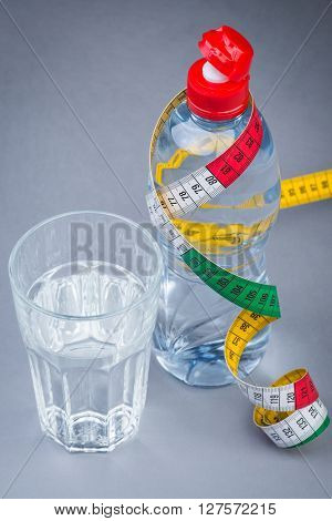 Bottle And Glass Of Fresh Still Water With Measuring Tape On Grey
