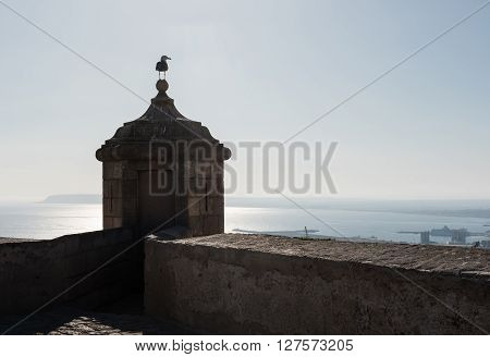 Turret and seagull against sea and blue sky background. Castle of Santa Barbara, main tourists attraction in Alicante city. Spain