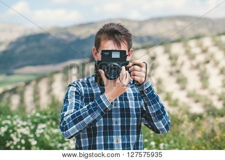 Man Taking A Picture With An Old Vintage Camera In The Countryside.