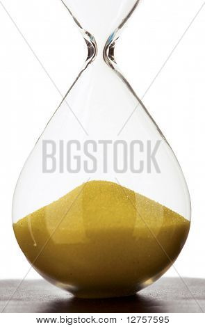 Close view of sand flowing through an hourglass.