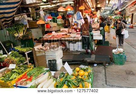 HONG KONG, CHINA - FEB 7, 2016: Customers of outdoor market choose seafood fruits and vegetables on busy narrow street on February 7, 2016. More than 47 million tourists visit Hong Kong annually
