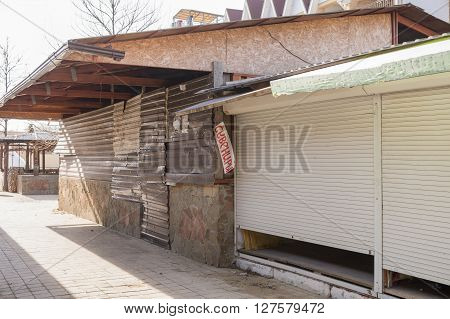 Closed Trade Pavilions And Boarded Metallosayding Building A Sidewalk Cafe On A Deserted Seaside Str