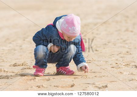 Five-year Girl In The Spring Of The Pen Draws On The Sand By The Sea