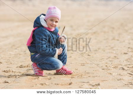 Five-year Girl Sat Down On The Sand By The Sea With Seagulls Pen In Hand