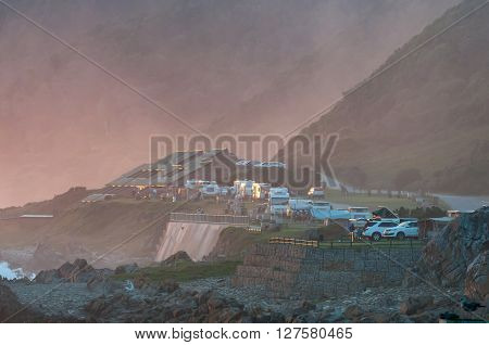STORMS RIVER MOUTH SOUTH AFRICA - MARCH 1 2016: Unidentified tourists at their caravans motorhomes and chalets in the last rays of the setting sun with fog from the sea rolling in