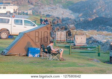 STORMS RIVER MOUTH SOUTH AFRICA - MARCH 1 2016: An unidentified tourist reading a book in the last rays of the sun at his tent at Storms River Mouth