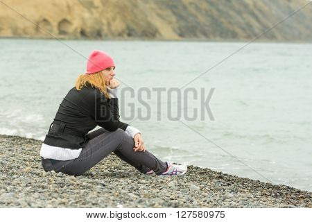 A Girl Sits On The Beach On A Cloudy Day In Cold Weather And Looking Thoughtfully Into The Distance