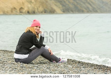 Sitting On The Beach On A Cool Cloudy Day Pretty Teenage Girl In A Pink Hat