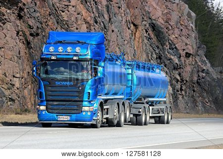 KARJAA, FINLAND - APRIL 10, 2016: Blue Scania R500 tank truck moves along highway with rock face on the background.