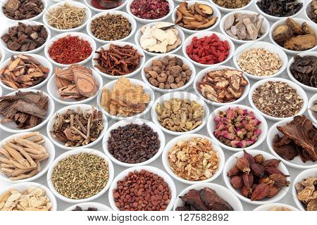 Large traditional chinese herbal medicine collection in porcelain bowls over white background.