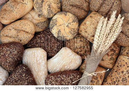 Bread roll selection with wheat sheaths in hessian forming an abstract background.